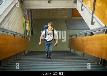 Boy wearing mask in school walking up stairs - Stock Photo