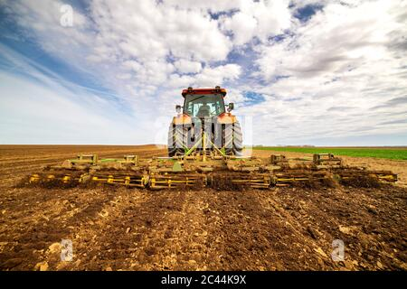 Back view of farmer in tractor plowing field in spring - Stock Photo