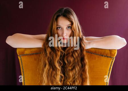 Portrait of young female fashion model with long brown wavy hair leaning on golden chair against colored background - Stock Photo