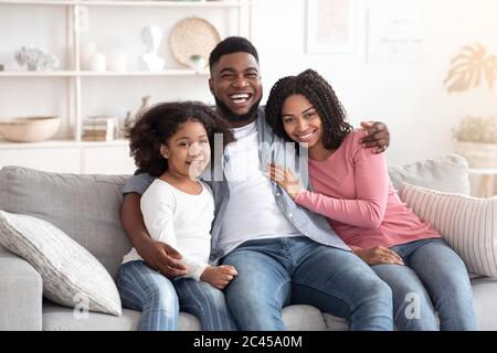 Family lifestyle portrait of happy black mom, dad and daughter at home - Stock Photo