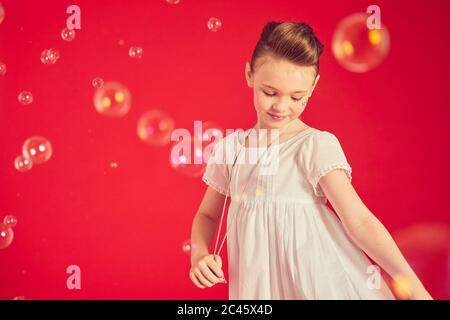 Portrait of brunette girl wearing romantic white dress on red background, surrounded by soap bubbles.