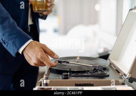 Businessman with iced drink, playing turntable in suite - Stock Photo