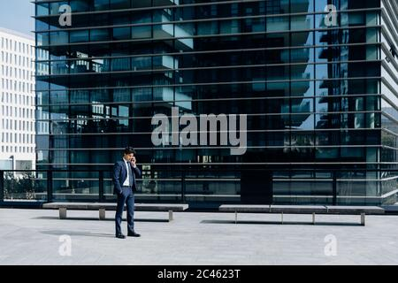 Businessman using smartphone in front of office building - Stock Photo