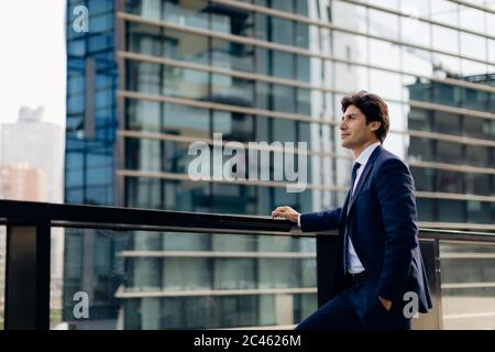 Businessman in front of office building - Stock Photo