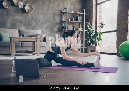 Full length profile side photo of focused beautiful sporty woman watch laptop aerobics intense effort balance video sit mat floor stretch legs hips - Stock Photo