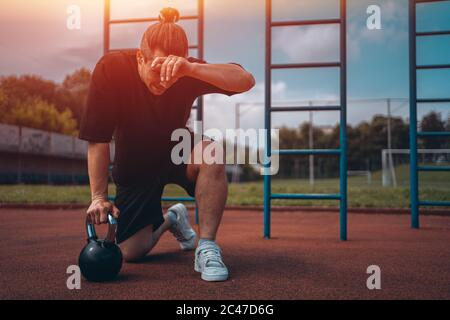 exhausted man athlete taking break between exercising with kettlebell outdoor - Stock Photo