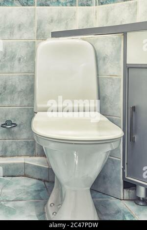 White mounted toilet bowl in modern bathroom with mirror and toilet brush - Stock Photo