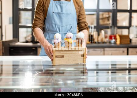 Seller putting a stand with three yummy ice creams in waffle cones with different flavor on the counter of a shop, close-up - Stock Photo