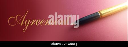 Agreemnt word in golden ink and Old-fashioned luxury pen on marsala color paper. Business conctract concept Stock Photo