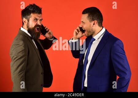 Businessmen with mad faces hold mobile phones. Business call concept. Machos in classic suits talk on cell phone. Men with beards stand face to face on red background. - Stock Photo