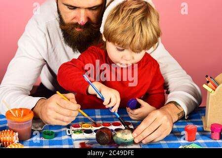 Easter celebration and joy concept. Man with beard and little boy painting eggs for Easter on pink background. Father and son preparing for holiday. Dad with painted nose make decorations