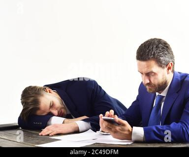 Overworked office worker lie on desk. Employees in formal suits look stressed and depressed. Men in with tired, worried faces surf internet. Overtime and frustration. Workaholic, deadline concept. - Stock Photo