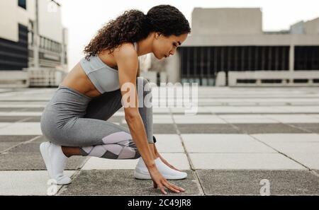 Side view of a female sprinter in start position outdoors in the city. Woman athlete in the starter position.
