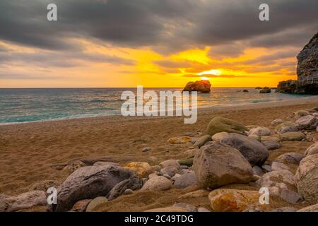 Coarse sand beach with stones. Colorful sunset over the calm sea - Stock Photo