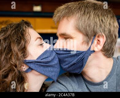 A young couple kiss while wearing masks to protect from coronavirus covid-19 love romance together relationship