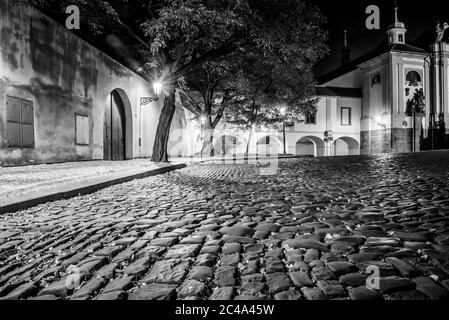 Narrow cobbled street in old medieval town with illuminated houses by vintage street lamps, Novy svet, Prague, Czech Republic. Night shot. Black and white image. - Stock Photo
