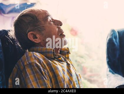 side portrait of an old man sitting at home with oxygen in his nose.