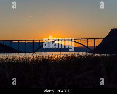 Sunset landscape silhouette silhouetting trees bridge mainland to island Krk Croatia - Stock Photo