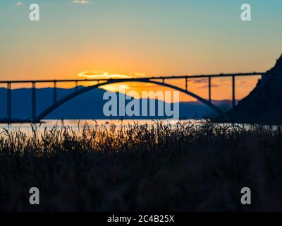 Sunset landscape silhouette silhouetting grass in foreground bridge mainland to island Krk Croatia - Stock Photo