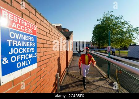 A general view as jockeys leave the weighing room and make their way to the parade ring at Leicester Racecourse.
