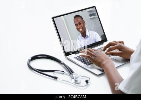 African Doctor In Video Conference Call Talking With Patient - Stock Photo