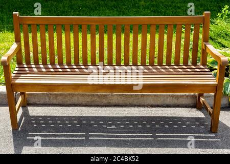 a wooden brown bench made of boards stands on an asphalt pavement near the curb with a green lawn in the park. - Stock Photo