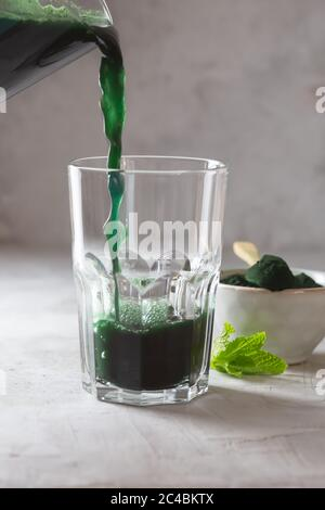 Green drink prepared with single celled green algae chlorella. Detox superfood in the glass - Stock Photo