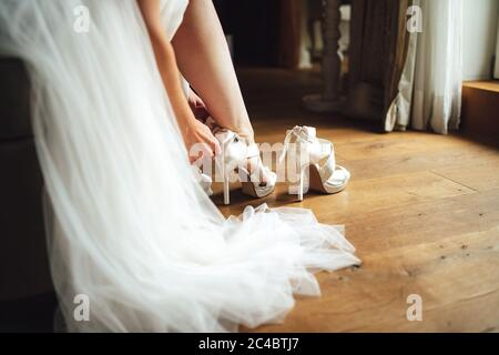 Bride putting on white shoes on her nice feet. Sitting woman in white wedding gown. Wedding shoes on wooden floor.
