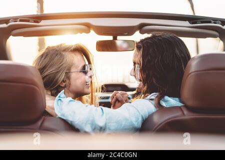 Happy young couple doing road trip in tropical city - Travel people having tender moments in trendy convertible car while discovering new places - Stock Photo