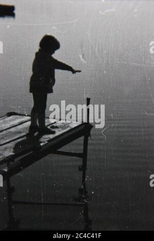 Fine 70s vintage contact print black and white photography of a child standing at the end of a pier looking at the still waters.