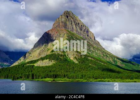 5044 Grinnell Point stands against a backdrop of clouds at Glacier National Park's Swiftcurrent Lake