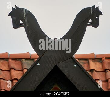 Horse heads carved from wood on the gable of a traditional Lower Saxon house - Stock Photo