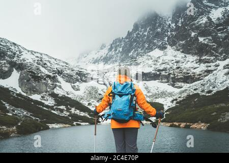Dressed bright orange jacket female backpacker with trekking poles enjoying the Velicke pleso (mountain lake) view during mountain walk in Velicka val