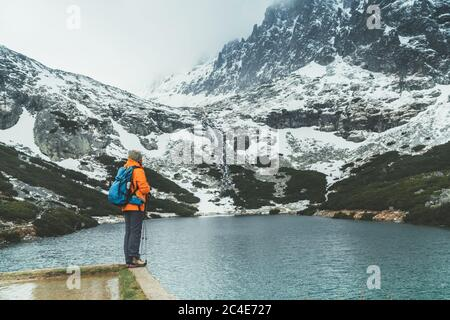 Dressed bright orange jacket female backpacker enjoying the Velicke pleso (mountain lake) view as she have mountain walk in Velicka valley in High Tat