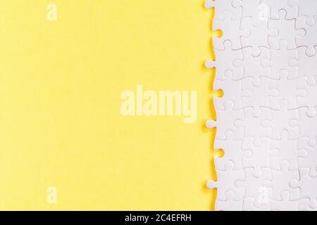 White jigsaw puzzle pieces on yellow. Abstract template and background with copy space - Stock Photo