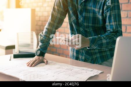 Architect standing typing on smartphone and working in modern office. - Stock Photo