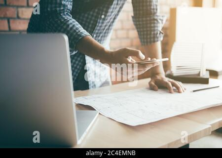Man standing typing on smartphone and working in modern office. - Stock Photo