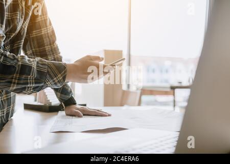 Man standing and message to customer on smartphone and working in modern office. - Stock Photo