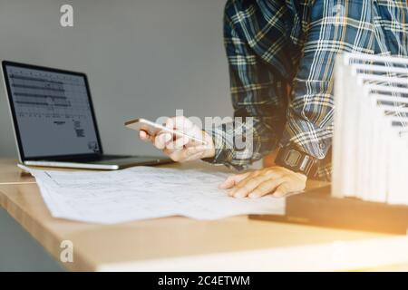 Engineering man standing and message to customer on smartphone and working in modern office. - Stock Photo