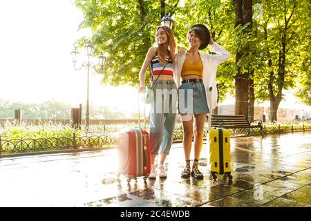 Photo of two happy beautiful women smiling and hugging while walking with suitcases at green city boulevard - Stock Photo