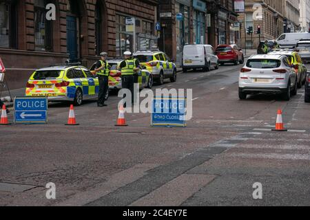 Glasgow, Scotland, UK. 26th June, 2020. Glasgow's West George Street and surrounding streets are locked down in a major police incident. 6 people have been critically injured, including a police officer, in a knife attack. The suspect in the attack was shot dead at the scene by armed police outside a hotel where asylum seekers are being housed. Credit: Richard Gass/Alamy Live News - Stock Photo