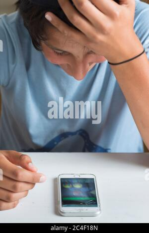 Teenage boy chats with friends on his smart phone - Stock Photo