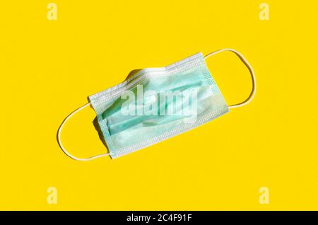 Medical or surgical face mask on a bright yellow background. - Stock Photo