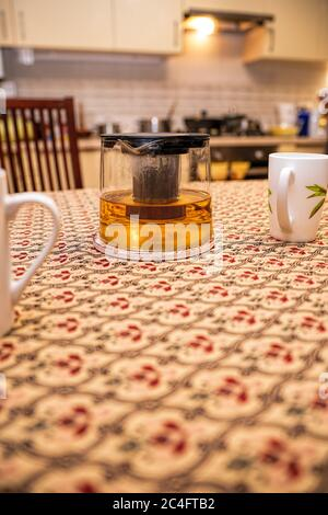 Glass custard with tea and cups on the kitchen table in the background of the kitchen. Place for text. The concept of happy family life. - Stock Photo