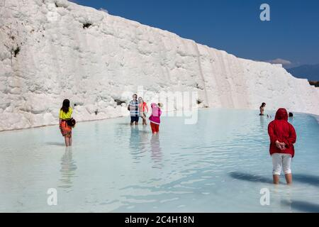 People stand in one of the thermal pools at the travertines, or Cotton Castle, at Pamukkale in Turkey. - Stock Photo
