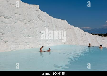 People relax in one of the thermal pools at the travertines, or Cotton Castle, at Pamukkale in Turkey. - Stock Photo