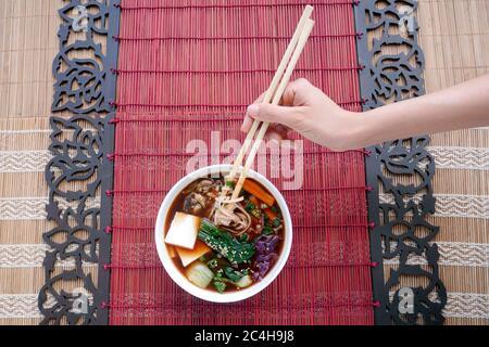 A WOMAN HOLDS JAPANESE  SHOYU RAMEN WITH CHOPSTICKS - Stock Photo