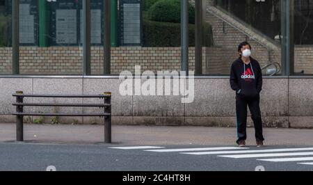 Man with mask standing in the street on Shinjuku, Tokyo, Japan - Stock Photo