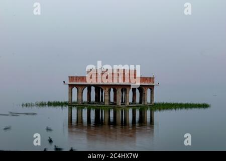 A flock of birds sitting on a pavilion in front of the Jal Mahal, Jaipur, Rajasthan, India - Stock Photo
