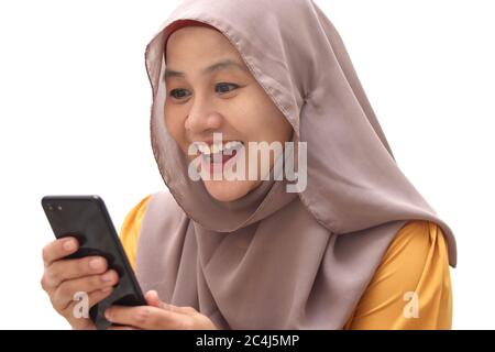 Close up portrait of young Asian muslim woman wearing hijab get good news on her phone, happy surprised expression, isolated on white - Stock Photo